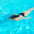 Stock Photo: Young womswimming underwater in swimming pool