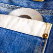 Compact disk on blue jeans — Stock Photo