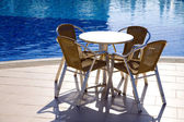 Table and chairs near a pool — 图库照片