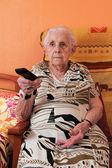 Senior woman and remote control — Stock Photo
