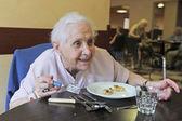 старший женщина ест — Стоковое фото