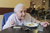 Senior woman eating — Stockfoto