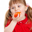 Foto Stock: Little girl eats tomato with appetite on white
