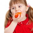 Little girl eats tomato with appetite on white — Photo #4135881