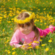 The girl in a wreath from dandelions on a grass — Stock Photo