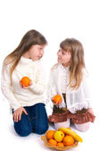 Two little girls with fruit on the white — Stock Photo