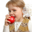 The little girl biting an apple — Stock Photo