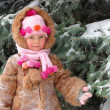 Girl in winter clothes at a snow-covered pine — Stock Photo
