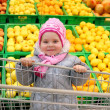 The girl with a basket in shop with fruit background — Stock Photo