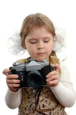 The little girl with the photo camera on the white — Stock Photo