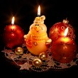 Burning candle and New Year's toys on a black background — Stock Photo #4275853
