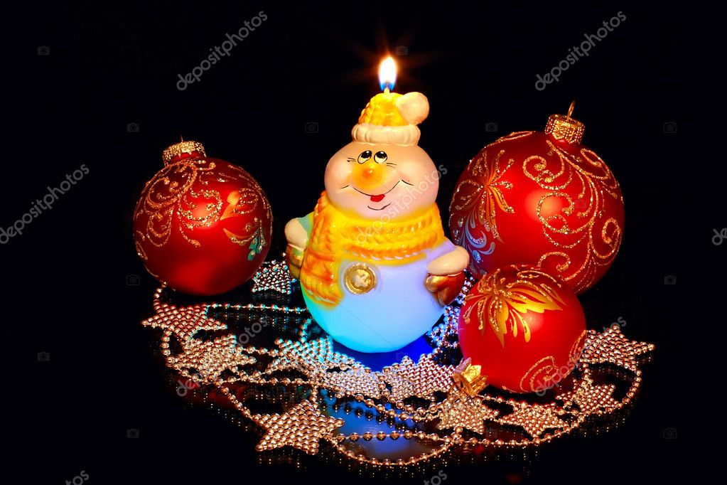 Burning candle and New Year's toys on a black background — Stock Photo #4275855