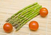 Aspargus and tamatos on bamboo substrate — Stok fotoğraf
