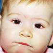 Royalty-Free Stock Photo: A young child is looking into the camera and sucking their lip.