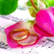 Gold wedding rings and pink rose on the note — Stock Photo