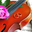 Wedding rings and pink roses with violin on the note — Stock Photo