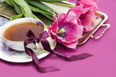 Violet tulips and cup of tea — Stock Photo