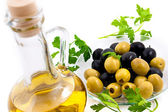 Olives and oil jug with greens — Stock Photo