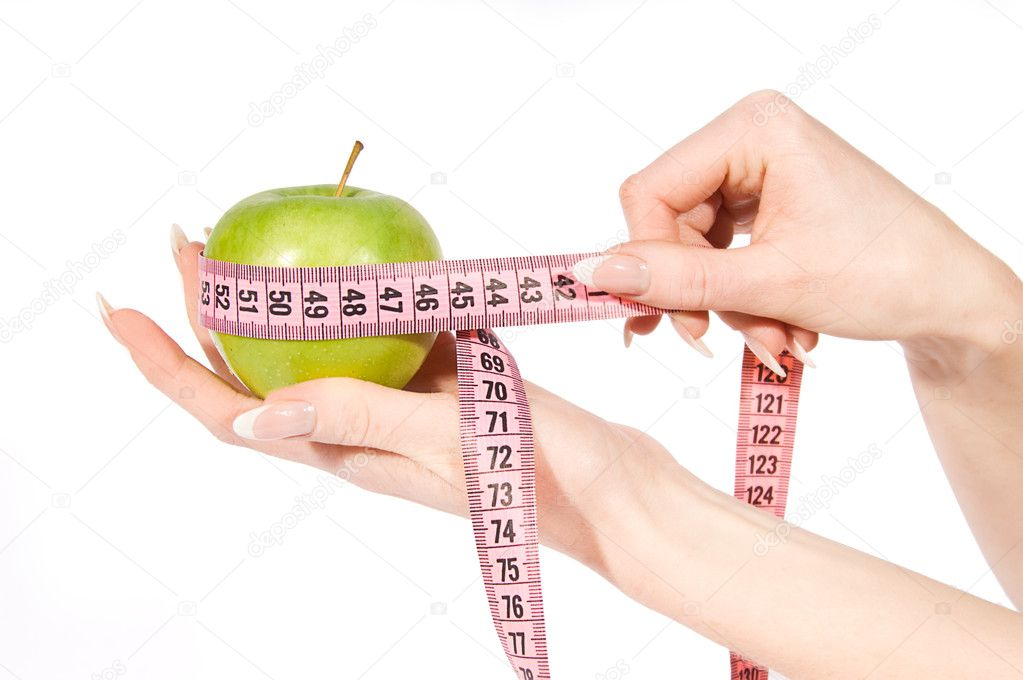 Woman hands measuring green apple over white  Stock Photo #5342343