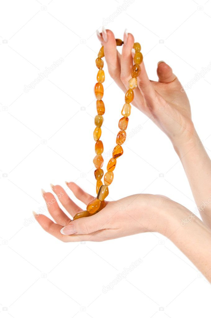 Woman hands holding amber necklace over white — Stock Photo #5356608