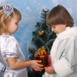 Foto de Stock  : Cute girl and a boy near a Christmas tree with gift in hand