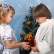 Foto Stock: Cute girl and a boy near a Christmas tree with gift in hand