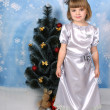 Stock Photo: Cute girl in a silver dress around Christmas tree