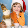Portrait of a beautiful girl in a Santa Claus hat with a rabbit — Stock Photo