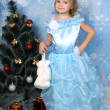 Stock Photo: Beautiful girl in a posh blue dress with fur around a Christmas