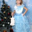 Beautiful girl in a posh blue dress with fur around a Christmas — Stock Photo