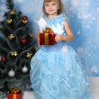 Beautiful girl in a posh blue dress around a Christmas tree with — Stock Photo #4338239