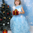 Beautiful girl in posh blue dress around Christmas tree with — Stock Photo #4338239