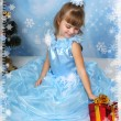 Stock Photo: Beautiful girl sat in a chic blue dress around a Christmas tree