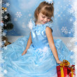 Beautiful girl sat in a chic blue dress around a Christmas tree — Stock Photo