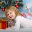 Beautiful girl with a gift lies near the Christmas tree — Stockfoto