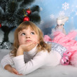 Beautiful girl with a gift lies near the Christmas tree — Stock Photo