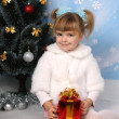 Beautiful girl in a fur cloak around the Christmas tree with gif — Stock Photo