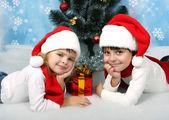 Красивые дети в новой шапки лежат под дерево — Стоковое фото