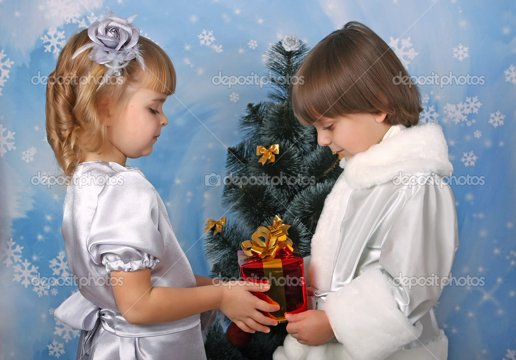 Cute girl and a boy near a Christmas tree with gift in hand  Stock Photo #4338098