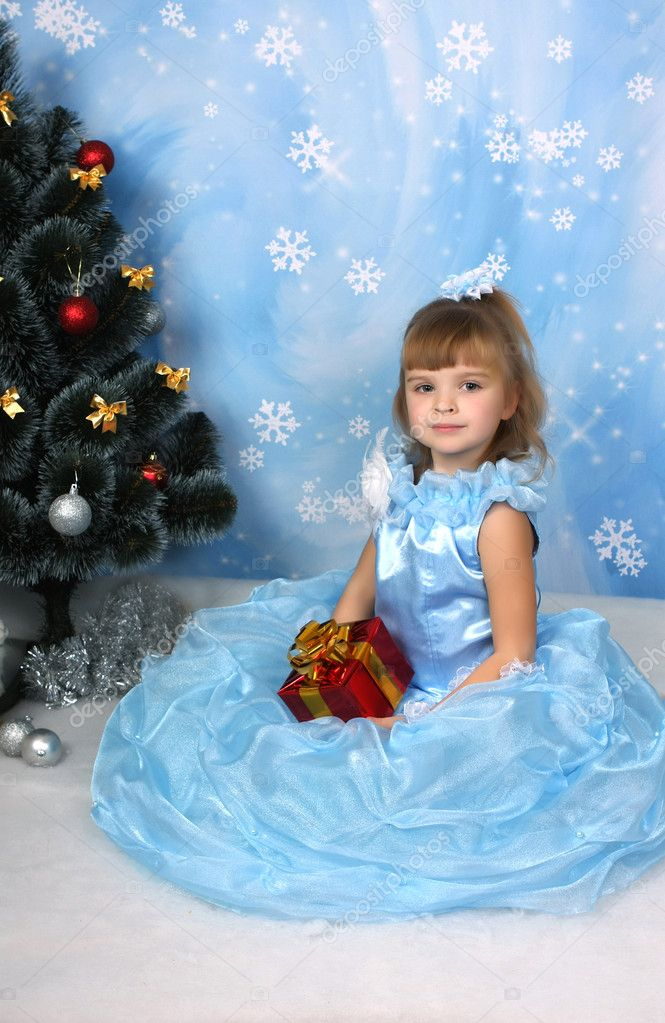 Beautiful girl sat in a chic blue dress around a Christmas tree with gift — Stock Photo #4338245