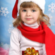 Portrait of a beautiful girl in a Santa Claus hat with a gift - Stock Photo