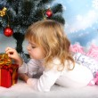 Beautiful girl with a gift lies near the Christmas tree - Stock Photo