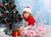 Beautiful girl in the hat of Santa Claus with a gift around the — Stock Photo