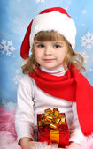 Portrait of a beautiful girl in a Santa Claus hat with a gift — Stock Photo