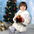 Boy near a Christmas tree with gift in hand - Lizenzfreies Foto