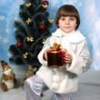 Boy near a Christmas tree with gift in hand - Stockfoto