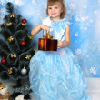 Beautiful girl in a posh blue dress around a Christmas tree with — Stock Photo