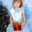 Beautiful girl in a posh blue dress around a Christmas tree with — Stock Photo #4487844