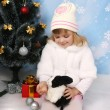 Little girl in a white coat and hat with a rabbit around a Chris — Stock Photo