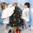 Boy and girl dressed as a silver dress decorate a Christmas tree — Stock Photo